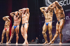 Bodybuilders show their abdominals and thighs pose in a lineup Stock Photos