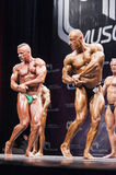 Bodybuilders show their chest pose on stage in championship Royalty Free Stock Photos