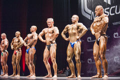 Bodybuilders show their lats spread pose in a lineup comparison Stock Photo