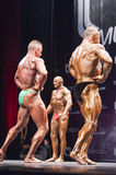 Bodybuilders show their lats spread pose on stage in championshi Royalty Free Stock Images