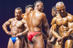 Bodybuilders show their physique on stage in championship Royalty Free Stock Image