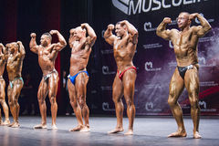 Bodybuilders show their physique on stage in championship Stock Photos