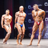 Bodybuilders show their physique on stage in championship Stock Photography