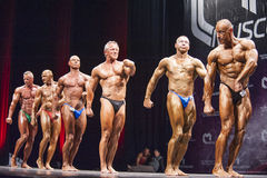 Bodybuilders show their side pose in a lineup comparison Royalty Free Stock Photo