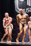 Bodybuilders show their triceps pose on stage in championship Stock Photography