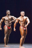 Bodybuilders shows his side chest pose on stage Royalty Free Stock Photography