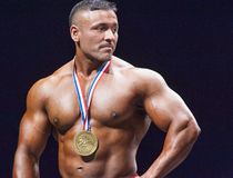 Bodybuilders shows his trophy on stage Royalty Free Stock Images