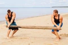 Bodybuilders sur la plage photos stock