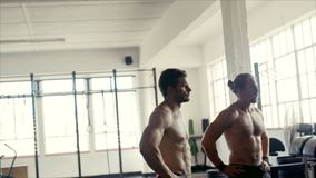 Bodybuilders taking a break after intense workout at gym. Two man doing standing in a cross fit gym. Bodybuilders taking a break after intense workout at fitness stock footage