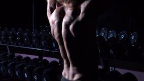 Bodybuildertraining in einer Turnhalle mit Dummköpfen und up seine Hände stock video footage