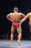 Bodybuildes shows his lats spread pose on stage Stock Photography