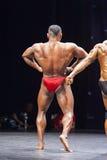 Bodybuildes toont zijn uitgespreid lats op stadium stelt Stock Fotografie
