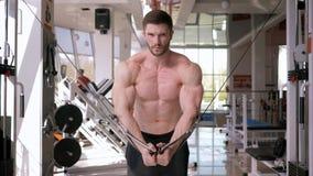 Bodybuilding, ισχυρός αθλητικός τύπος που κάνει την κατάρτιση οικοδόμησης μυών στον προσομοιωτή έλξης για τα χέρια λειτουργώντας  απόθεμα βίντεο