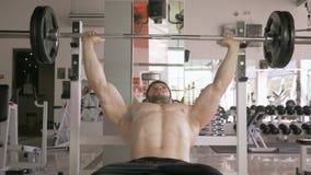 Bodybuilding, ισχυρό μυϊκό άτομο που κάνει τον Τύπο πάγκων με το barbell ενώ ο αθλητισμός που επιλύει στον αθλητισμό στρέφεται απόθεμα βίντεο