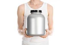 Bodybuilding και αθλητικό θέμα: ένα λεπτό άτομο σε μια άσπρη μπλούζα και τα τζιν που κρατά ένα πλαστικό βάζο με μια πρωτεΐνη που  στοκ φωτογραφίες με δικαίωμα ελεύθερης χρήσης