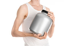 Bodybuilding και αθλητικό θέμα: ένα λεπτό άτομο σε μια άσπρη μπλούζα και τα τζιν που κρατά ένα πλαστικό βάζο με μια πρωτεΐνη που  στοκ φωτογραφία