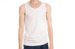 Bodybuilding και αθλητικό θέμα: ένα λεπτό άτομο σε μια άσπρη μπλούζα και τα τζιν στο λευκό απομόνωσαν το υπόβαθρο στο στούντιο στοκ εικόνες