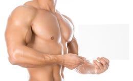 Bodybuilding και διαφήμιση: ένα συμπαθητικό ισχυρό bodybuilder που κρατά μια άσπρη κενή κάρτα εγγράφου απομονωμένη στο άσπρο υπόβ στοκ εικόνα με δικαίωμα ελεύθερης χρήσης