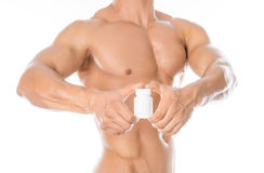 Bodybuilding και χημικές πρόσθετες ουσίες: το όμορφο ισχυρό bodybuilder που κρατά ένα άσπρο βάζο των χαπιών στο λευκό απομόνωσε τ Στοκ εικόνα με δικαίωμα ελεύθερης χρήσης