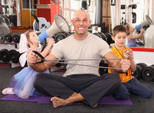 Bodybuilding. Kids training their father in a gym Royalty Free Stock Photography