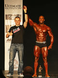 Bodybuilding Champ Earns Trophy. Handsome, rugged bodybuilder Harry Freeman III raises his arm in victory at the Classic Physique finals of the 2016 NPC Universe Royalty Free Stock Image