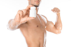 Bodybuilding and chemical additives: handsome strong bodybuilder holding a white jar of pills on white isolated background in stud Royalty Free Stock Images