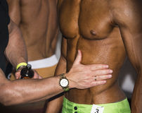 Bodybuilding competition backstage: contestant being oiled Royalty Free Stock Image