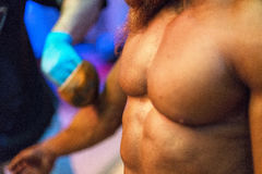 Bodybuilding competition backstage: contestant being oiled and fake tan applied to skin Stock Photography