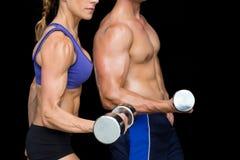 Bodybuilding couple posing with large dumbells Stock Photo