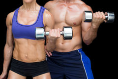 Bodybuilding couple posing with large dumbells Stock Photos