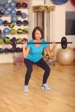 bodybuilding donna che si esercita con il bilanciere nella classe di forma fisica Allenamento femminile in palestra che fa gli ed Fotografia Stock