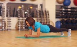 bodybuilding donna che si esercita sulla stuoia nella classe di forma fisica Allenamento femminile in palestra che fa plancia Fotografia Stock