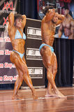 Bodybuilding duo in abdominals and thighs pose on stage Royalty Free Stock Image