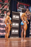 Bodybuilding duo in relaxed side pose on stage Stock Photo