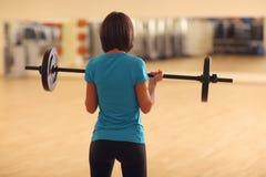 bodybuilding Frau, die mit Barbell trainiert anhebende Gewichte des Mädchens in der Turnhalle Stockbilder