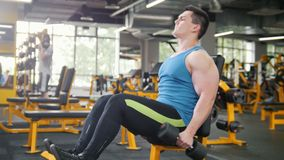 Bodybuilding in the gym - young sporty man performs training for arm with dumbbells stock footage