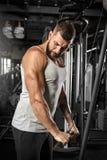 bodybuilding Homem farpado que está o pulldown reto doingcable do braço no gym concentrado fotos de stock royalty free
