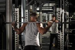 bodybuilding Homem farpado que exercita com o barbell no gym que olha o espelho motivado imagens de stock royalty free