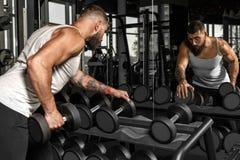 bodybuilding Homem farpado que exercita no gym com o peso que olha o espelho que verifica a opinião lateral da técnica fotos de stock