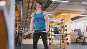 Bodybuilding i idrottshallen - den muskulösa mannen som utbildar hans biceps nära, avspeglar Arkivfoto