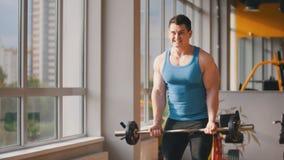 Bodybuilding i idrottshallen - muskulös man som utbildar upp hans biceps, slut Royaltyfri Bild