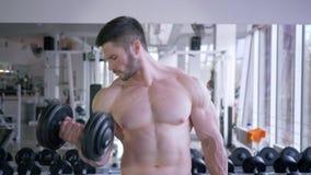 Bodybuilding idrottsman nenman som gör styrkaövning med hantlar i händer under maktgenomköraren för muskeln som in bygger stock video