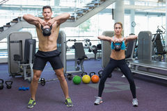 Bodybuilding man and woman lifting kettlebells Stock Images