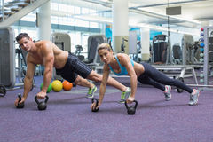 Bodybuilding man and woman lifting kettlebells in plank position Stock Photography