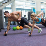 Bodybuilding man and woman lifting kettlebells in plank position Royalty Free Stock Photos