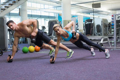 Bodybuilding man and woman lifting kettlebells in plank position Royalty Free Stock Image