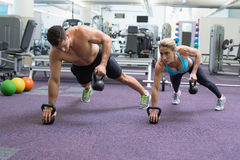 Bodybuilding man and woman lifting kettlebells in plank position Royalty Free Stock Photography