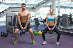 Bodybuilding man and woman lifting kettlebells in a squat Royalty Free Stock Photos