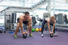 Bodybuilding man and woman lifting kettlebells in a squat Royalty Free Stock Images