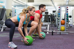 Bodybuilding man and woman lifting medicine balls doing squats Royalty Free Stock Image